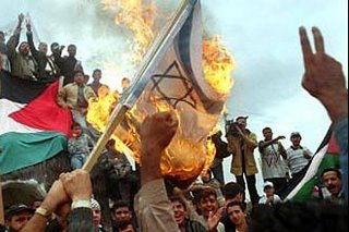Ikhwanul Muslimin (Muslim Brotherhood) protestors burning the Israeli flag